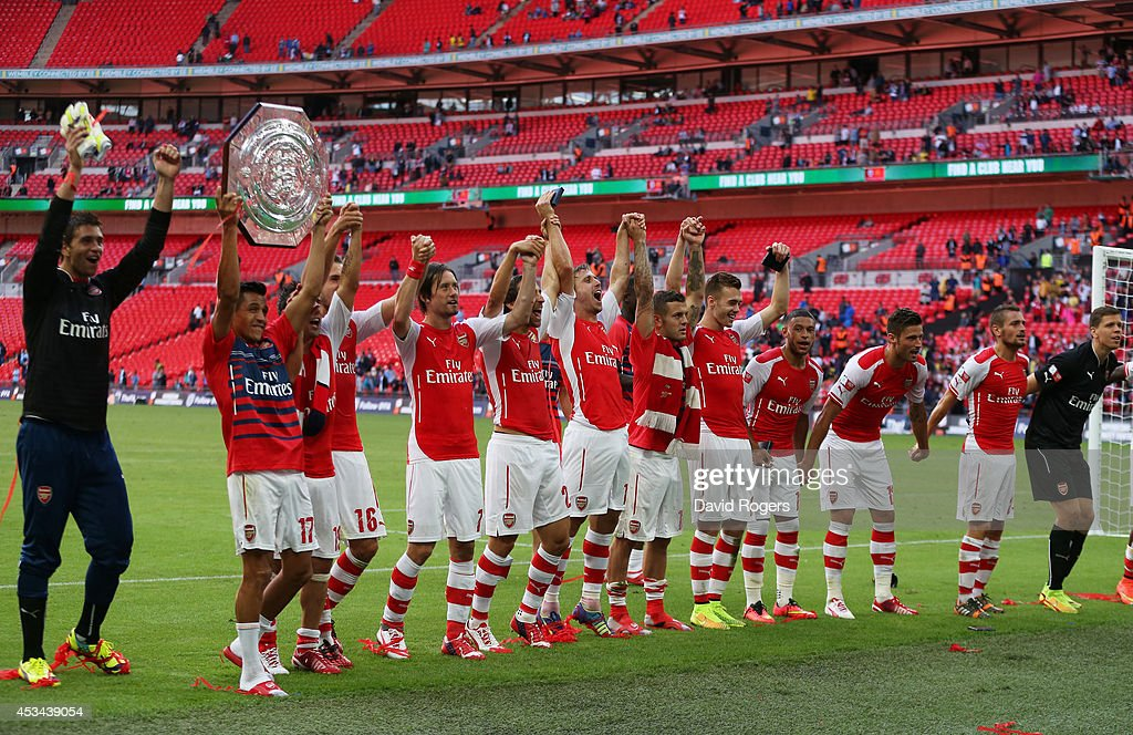 Alexis Sanchez of Arsenal holds up the trophy next to team-mates after the FA Community Shield match between Manchester City and Arsenal at Wembley Stadium on August 10, 2014 in London, England.