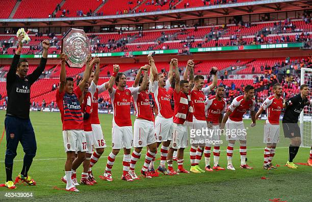 Alexis Sanchez of Arsenal holds up the trophy next to teammates after the FA Community Shield match between Manchester City and Arsenal at Wembley...
