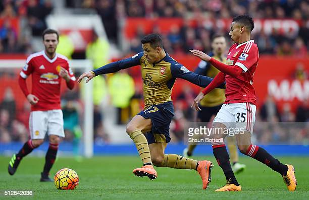 Alexis Sanchez of Arsenal is challenged by Jesse Lingard of Manchester United during the Barclays Premier League match between Manchester United and...