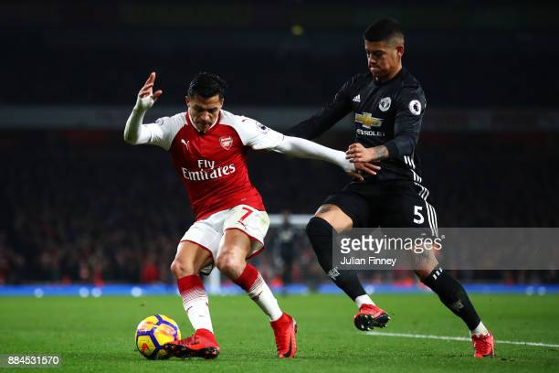 Alexis Sanchez of Arsenal is challenged by Marcos Rojo of Manchester United during the Premier League match between Arsenal and Manchester United at...