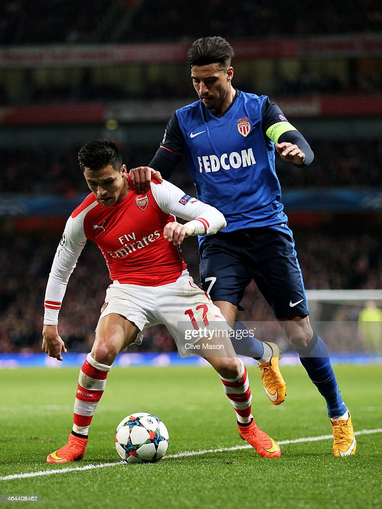 Alexis Sanchez of Arsenal is challenged by Nabil Dirar of Monaco during the UEFA Champions League round of 16, first leg match between Arsenal and Monaco at The Emirates Stadium on February 25, 2015 in London, United Kingdom.