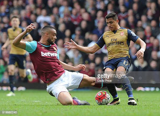 Alexis Sanchez of Arsenal is challenged by Winston Reid of West Ham during the Barclays Premier League match between West Ham United and Arsenal at...