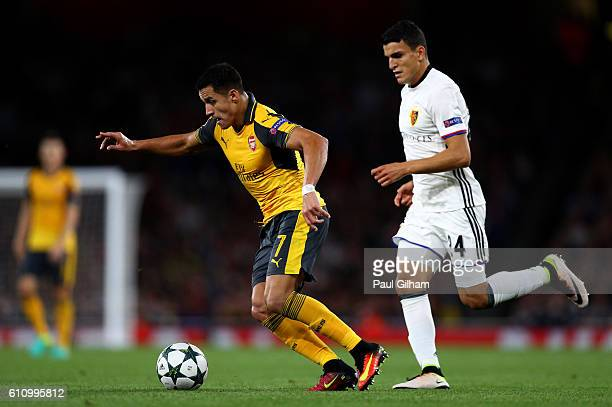 Alexis Sanchez of Arsenal is chased down by Mohamed Elyounoussi of Basel during the UEFA Champions League group A match between Arsenal FC and FC...