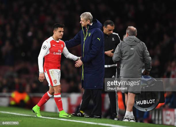 Alexis Sanchez of Arsenal is consoled by Arsene Wenger Manager of Arsenal as he is substituted during the UEFA Champions League Round of 16 second...