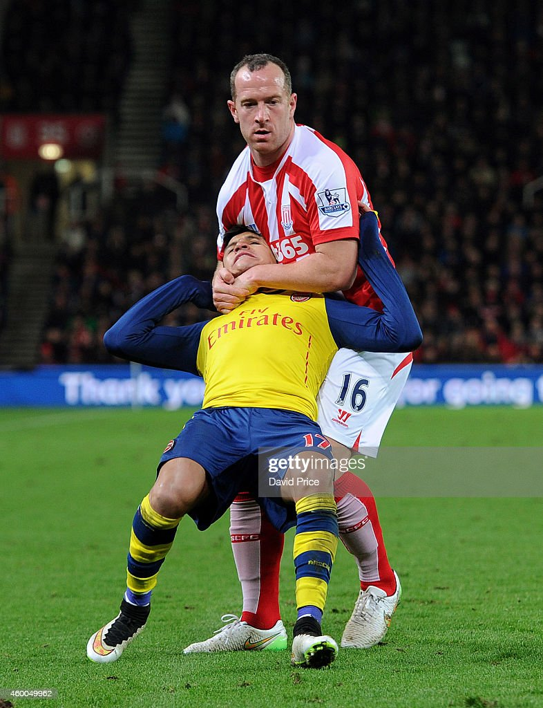 Alexis Sanchez of Arsenal is fouled by Charlie Adam of Stoke during the match between Stoke City and Arsenal in the Barclays Premier League at Britannia Stadium on December 6, 2014 in Stoke on Trent, England.