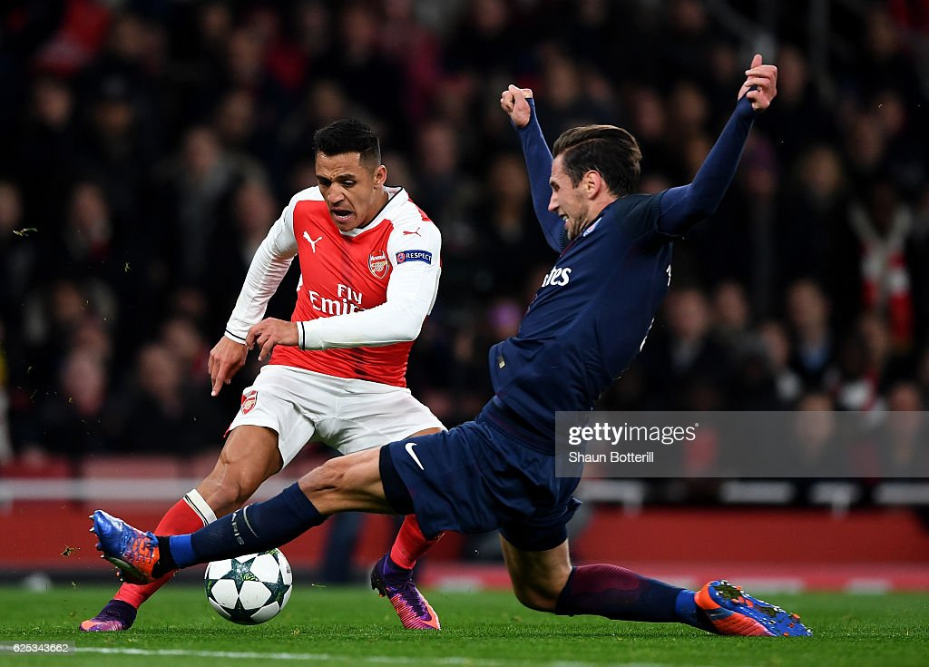 Alexis Sanchez of Arsenal (L) is fouled by Grzegorz Krychowiak of PSG (R) and a penalty is awarded to Arsenal during the UEFA Champions League Group A match between Arsenal FC and Paris Saint-Germain at the Emirates Stadium on November 23, 2016 in London, England.
