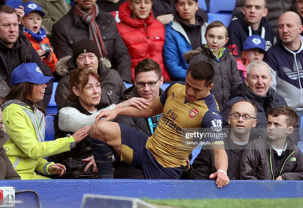 Alexis Sanchez of Arsenal is helped up by Everton supporters after he fell over the advertising boards during the Barclays Premier League match between Everton and Arsenal at Goodison Park on March 19, 2016 in Liverpool, England.