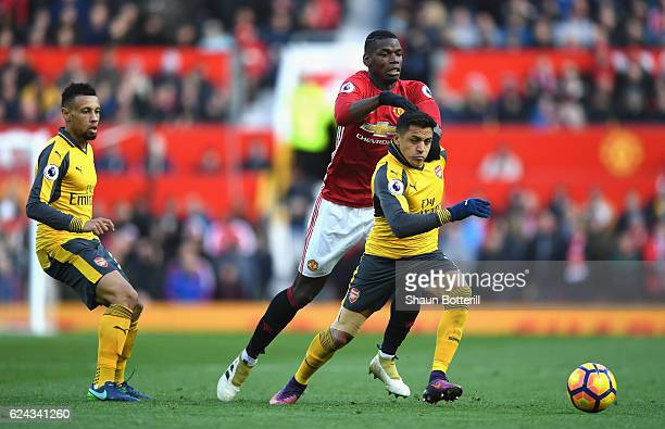 Alexis Sanchez of Arsenal is pulled back by Paul Pogba of Manchester United during the Premier League match between Manchester United and Arsenal at...