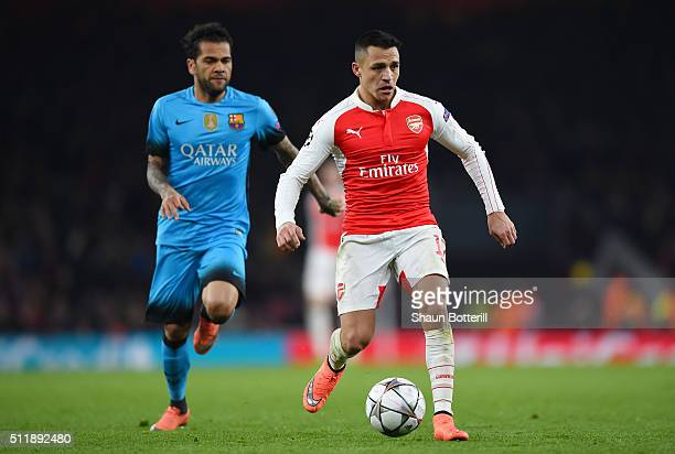 Alexis Sanchez of Arsenal is pursued by Dani Alves of Barcelona during the UEFA Champions League round of 16 first leg match between Arsenal FC and...