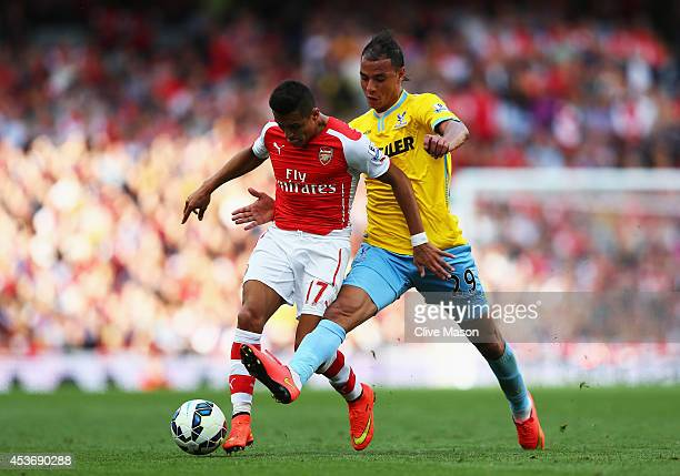 Alexis Sanchez of Arsenal is tackled by Marouane Chamakh of Crystal Palace during the Barclays Premier League match between Arsenal and Crystal...