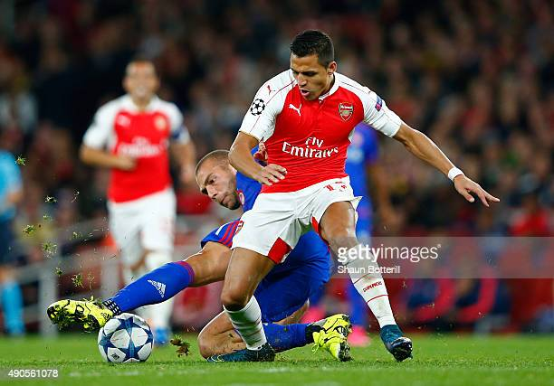 Alexis Sanchez of Arsenal is tackled by Pajtim Kasami of Olympiacos during the UEFA Champions League Group F match between Arsenal FC and Olympiacos...
