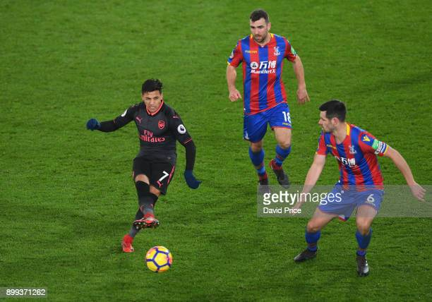 Alexis Sanchez of Arsenal passes the ball under pressure from Scott Dan and James McArthur of Palace during the Premier League match between Crystal...