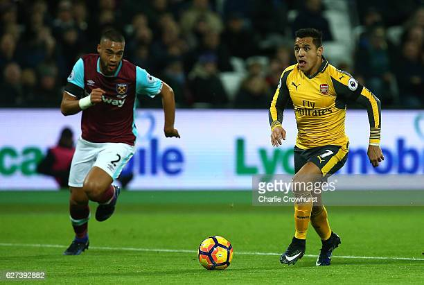 Alexis Sanchez of Arsenal runs with the ball under pressure from Winston Reid of West Ham during the Premier League match between West Ham United and...