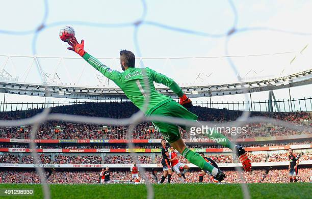 Alexis Sanchez of Arsenal scores Arsenal's third goal past the outstretched David De Gea of Manchester United during the Barclays Premier League...