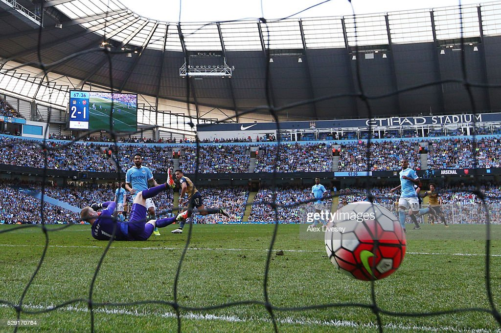 Alexis Sanchez of Arsenal (c) scores his side's second goal past Joe Hart of Manchester City during the Barclays Premier League match between Manchester City and Arsenal at the Etihad Stadium on May 8, 2016 in Manchester, England.