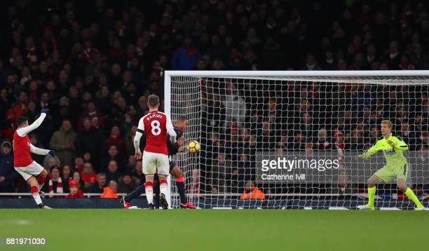Alexis Sanchez of Arsenal scores his sides third goal during the Premier League match between Arsenal and Huddersfield Town at Emirates Stadium on...