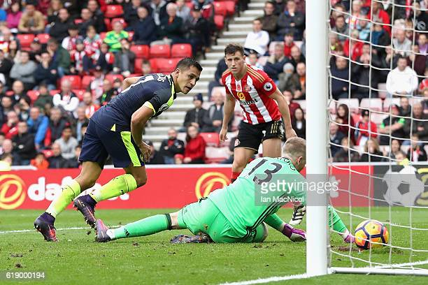 Alexis Sanchez of Arsenal scores his team's fourth goal past Jordan Pickford of Sunderland during the Premier League match between Sunderland and...