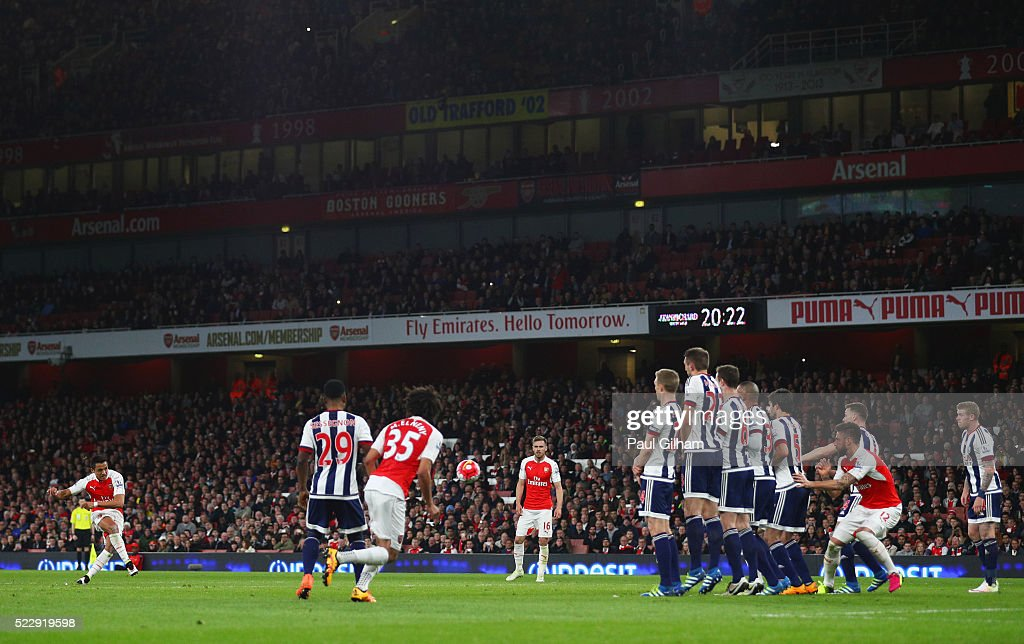Alexis Sanchez of Arsenal (L) scores their second goal from a free kick during the Barclays Premier League match between Arsenal and West Bromwich Albion at the Emirates Stadium on April 21, 2016 in London, England.