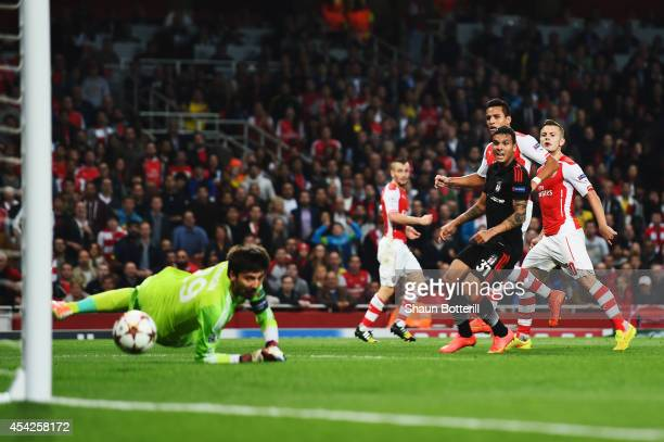Alexis Sanchez of Arsenal shoots and scores past Tolga Zengin the Besiktas goalkeeper during the UEFA Champions League Qualifier 2nd leg match...