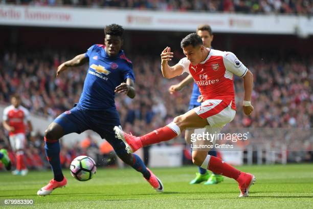 Alexis Sanchez of Arsenal shoots as Axel Tuanzebe of Manchester United attempts to block during the Premier League match between Arsenal and...