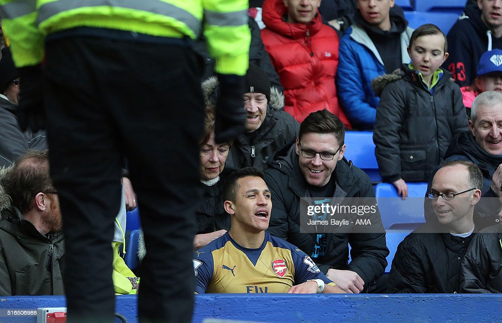 Alexis Sanchez of Arsenal sits in a seat to watch the match after falling over an advertising board into the crowd during the Barclays Premier League match between Everton and Arsenal at Goodison Park on March 19, 2016 in Liverpool, England.