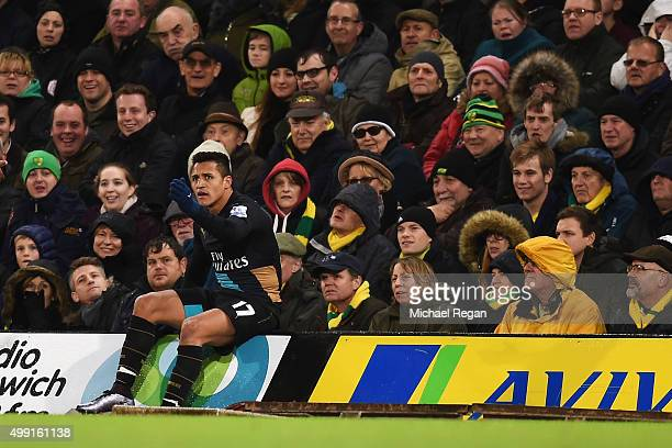 Alexis Sanchez of Arsenal sits on a hoarding during the Barclays Premier League match between Norwich City and Arsenal at Carrow Road on November 29...