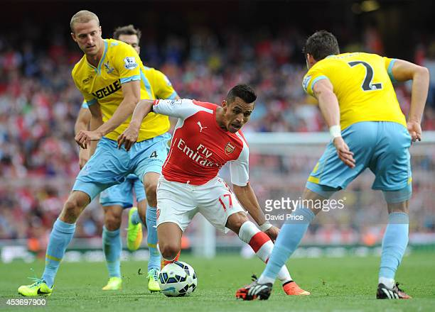 Alexis Sanchez of Arsenal takes on Brede Hangeland and Joel Ward of Palace during the Barclays Premier League match between Arsenal and Crystal...