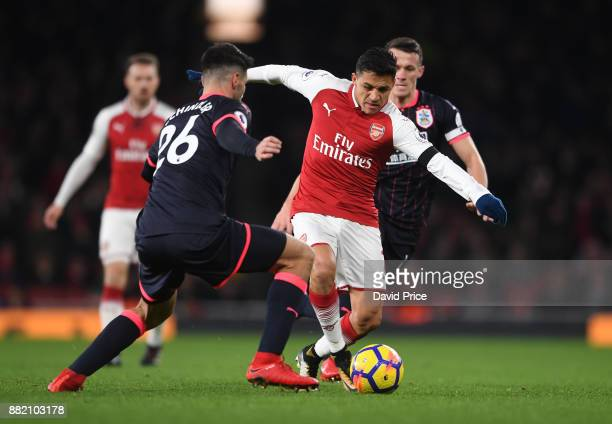 Alexis Sanchez of Arsenal takes on Christopher Schindler of Huddersfield during the Premier League match between Arsenal and Huddersfield Town at...
