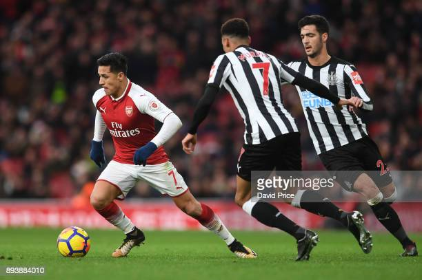 Alexis Sanchez of Arsenal takes on Jacob Murphy and Mikel Merino of Newcastle during the Premier League match between Arsenal and Newcastle United at...