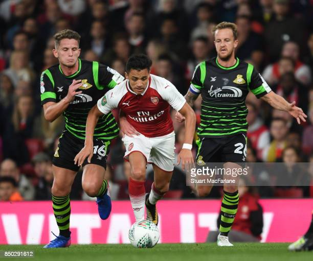 Alexis Sanchez of Arsenal takes on Jordan Houghton and James Coppinger of Doncaster during the Carabao Cup Third Round match between Arsenal and...