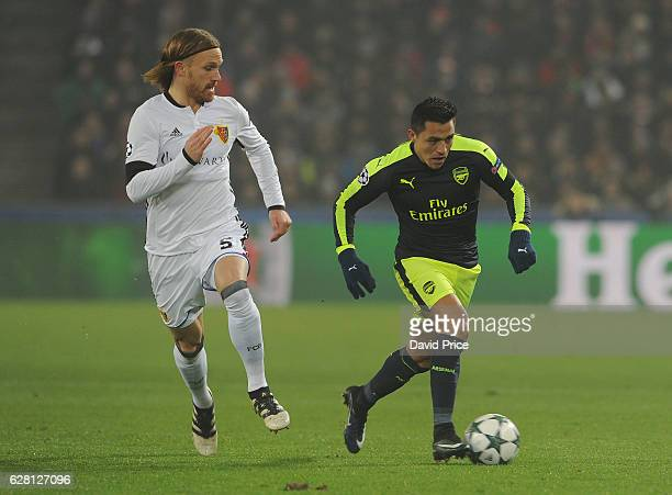 Alexis Sanchez of Arsenal takes on Michael Lang of Basel during the UEFA Champions League match between FC Basel and Arsenal at St JakobPark on...