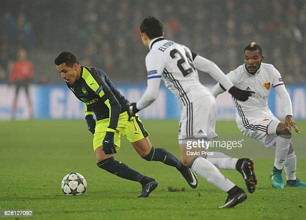 Alexis Sanchez of Arsenal takes on Mohamed Elyounoussi and Geoffroy Serey of Basel during the UEFA Champions League match between FC Basel and...