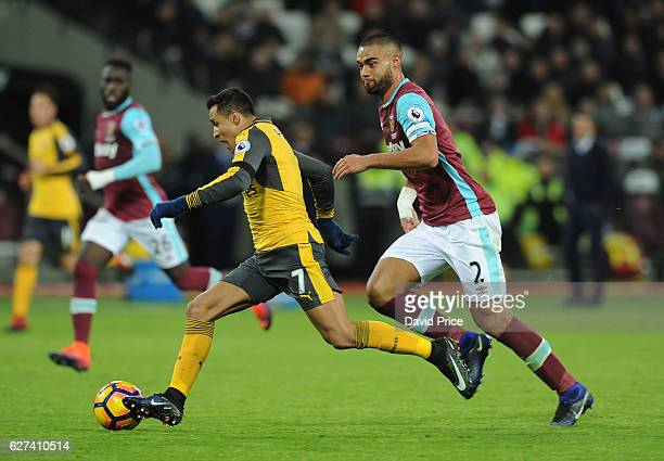 Alexis Sanchez of Arsenal takes on Winston Reid of West Ham during the Premier League match between West Ham United and Arsenal at London Stadium on...
