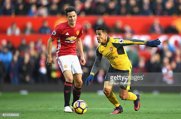 Alexis Sanchez of Arsenal takes the ball past Ander Herrera of Manchester United during the Premier League match between Manchester United and...