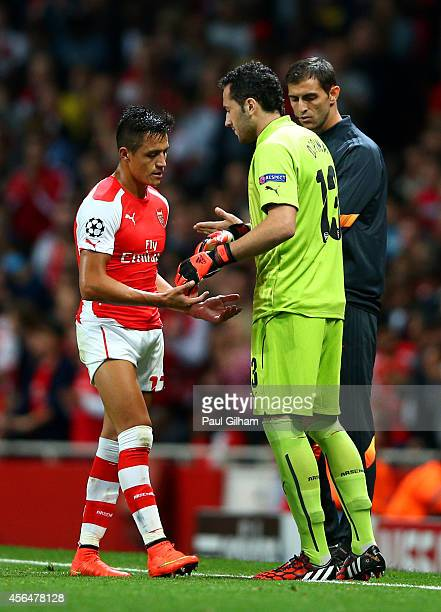Alexis Sanchez of Arsenal taps hands with David Ospina as he is substituted following Wojciech Szczesny's red card during the UEFA Champions League...