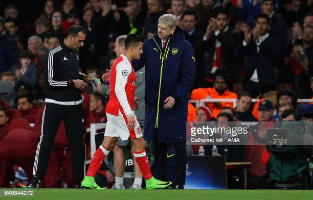 Alexis Sanchez of Arsenal walks past Arsene Wenger manager of Arsenal during the UEFA Champions League Round of 16 second leg match between Arsenal...