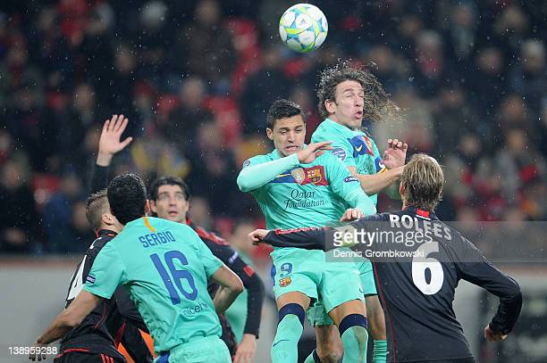 Alexis Sanchez of Barcelona and teammate Carles Puyol jump for a header during the UEFA Champions League round of sixteen first leg match between...