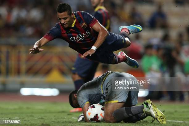 Alexis Sanchez of Barcelona dives over goalkeeper Watchara Buathong of Thailand XI during the international friendly match between Thailand XI and FC...