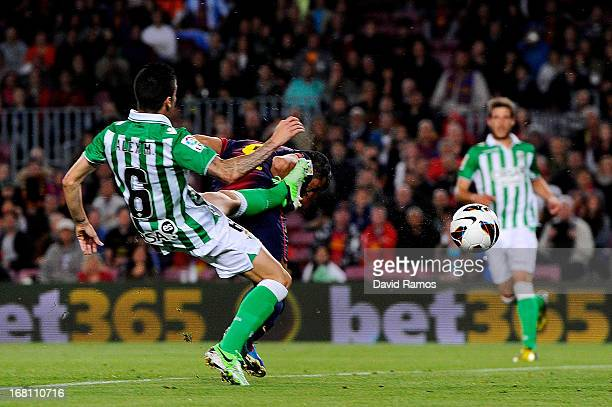 Alexis Sanchez of Barcelona scores a goal with a header to level the scores at 11 despite the attentions of Alex Martinez of Real Betis during the La...