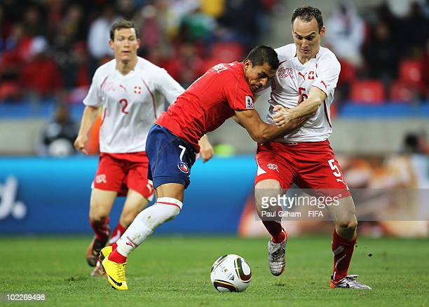 Alexis Sanchez of Chile and Steve von Bergen of Switzerland battle for the ball during the 2010 FIFA World Cup South Africa Group H match between...
