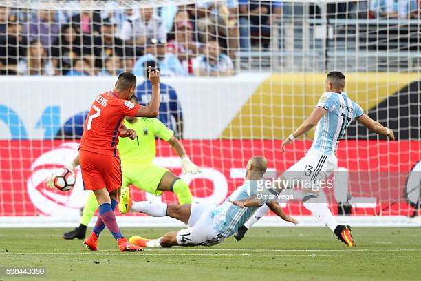 Alexis Sanchez of Chile attempts to score past Sergio Romero goalkeeper of Argentina as Javier Mascherano and Ramiro Funes Mori of Argentina defend...