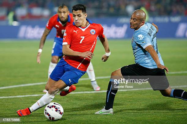 Alexis Sanchez of Chile fights for the ball with Egidio Arevalo of Uruguay during the 2015 Copa America Chile quarter final match between Chile and...