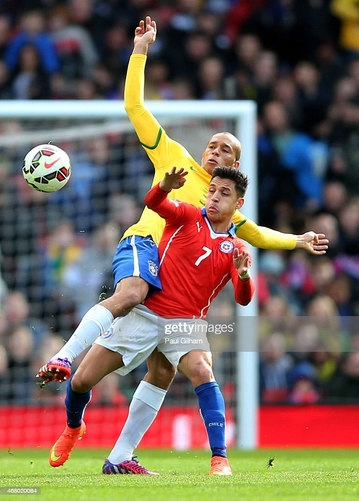 Alexis Sanchez of Chile is tackled by Miranda of Brazil during the international friendly match between Brazil and Chile at the Emirates Stadium on March 29, 2015 in London, England.