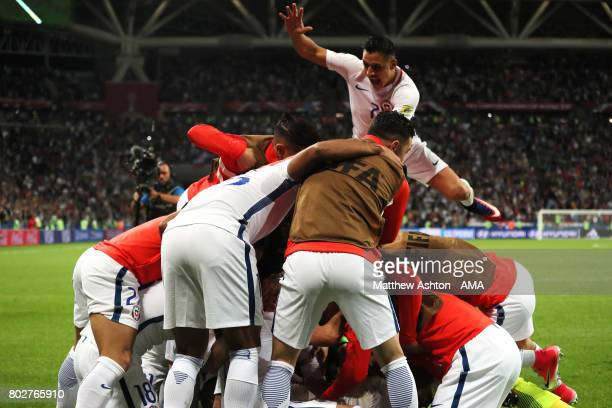 Alexis Sanchez of Chile jumps on to Claudio Bravo with his teammates as they celebrate winning a penalty shootout during the FIFA Confederations Cup...