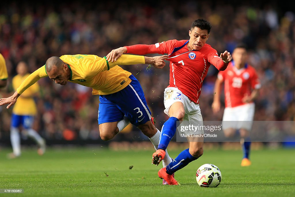 Alexis Sanchez of Chile tangles with Miranda of Brazil during the international friendly match between Brazil and Chile at the Emirates Stadium on March 29, 2015 in London,