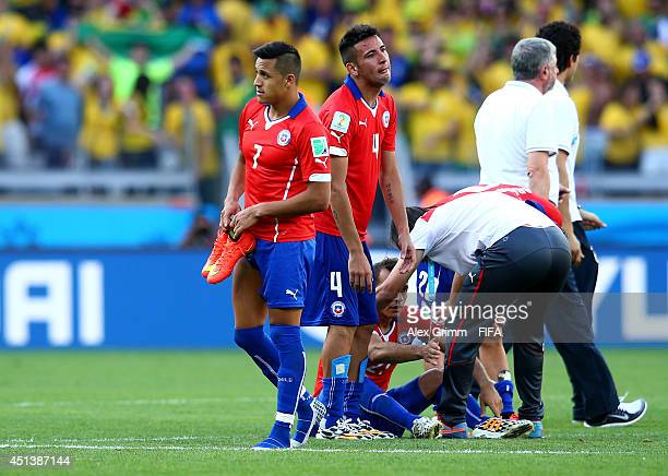 Alexis Sanchez of Chile walks off the pitch after the defeat through the penalty shootout in the 2014 FIFA World Cup Brazil Round of 16 match between...