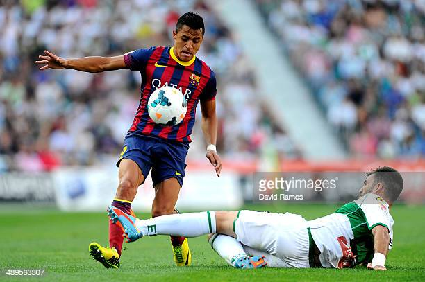 Alexis Sanchez of FC Barcelona competes for the ball Domingo Cisma of Elche FC during the La Liga match between Elche FC and FC Barcelona at Estadio...