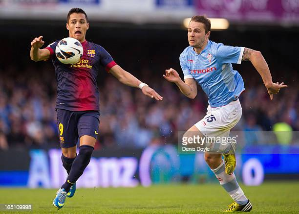 Alexis Sanchez of FC Barcelona controls the ball beside Marc Bartra of RC Celta de Vigo of during the La Liga match between RC Celta de Vigo and FC...