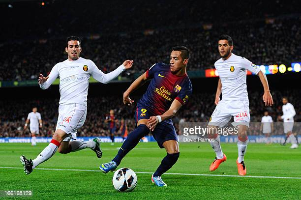 Alexis Sanchez of FC Barcelona duels for the ball with Alejandro Alfaro and Kevin Garcia of RCD Mallorcaduring the La Liga match between FC Barcelona...