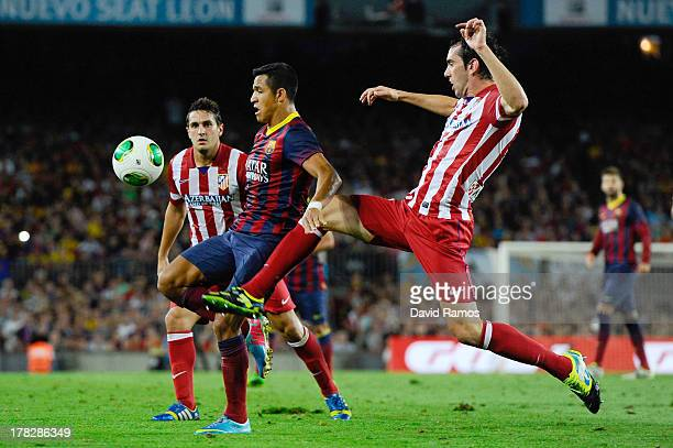 Alexis Sanchez of FC Barcelona duels for the ball with Diego Godin of Atletico de Madrid during the Spanish Super Cup second leg match between FC...